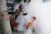 A resident holds his nose and portable radio as he tries to avoid disinfectants sprayed in the neighborhood as a precaution against the spread of COVID-19 in Manila, Philippines on Monday, March 15, 2021. The Department of Health has been reporting a surge in infections for more than a week, adding to concerns over a sluggish start of a vaccination campaign that has faced supply problems and public reluctance. (AP Photo/Aaron Favila)