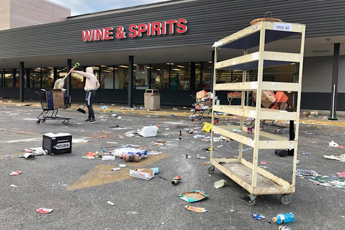 A person cleans up items outside a Jewel grocery store Monday, June 1, 2020, in the Bronzeville neighborhood of Chicago, after the business was broken into during unrest in reaction to the death of George Floyd. Floyd died after being restrained by Minneapolis police officers on May 25.