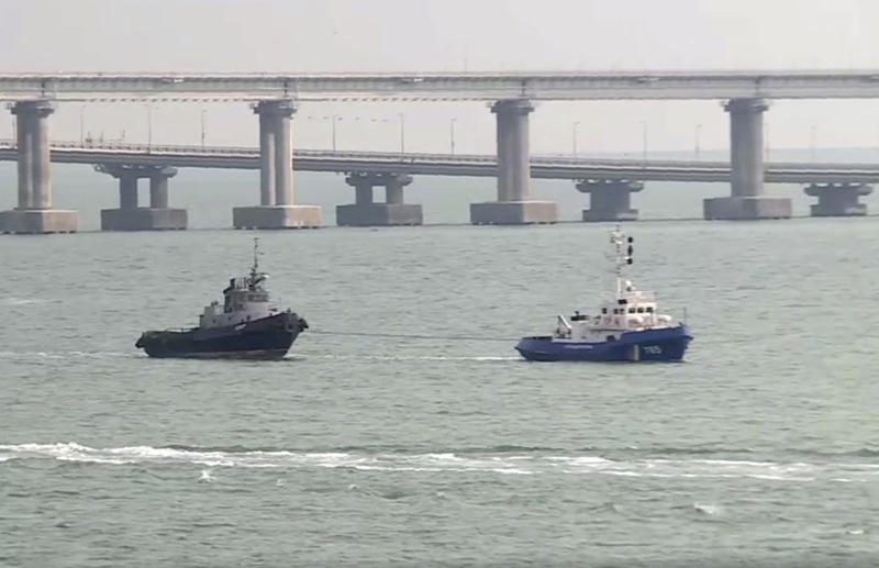 This video grab provided by the Krym 24 tv station via AP Television shows a seized Ukrainian ship, left, is towed by a Russian coast guard boat out of the port in Kerch, Crimea, with the Kerch bridge in the background, Sunday, Nov. 17, 2019. Russia's Foreign Ministry says three Ukrainian naval ships that were seized in a shooting confrontation nearly a year ago have been returned. (Krym 24 tv station via AP Television)