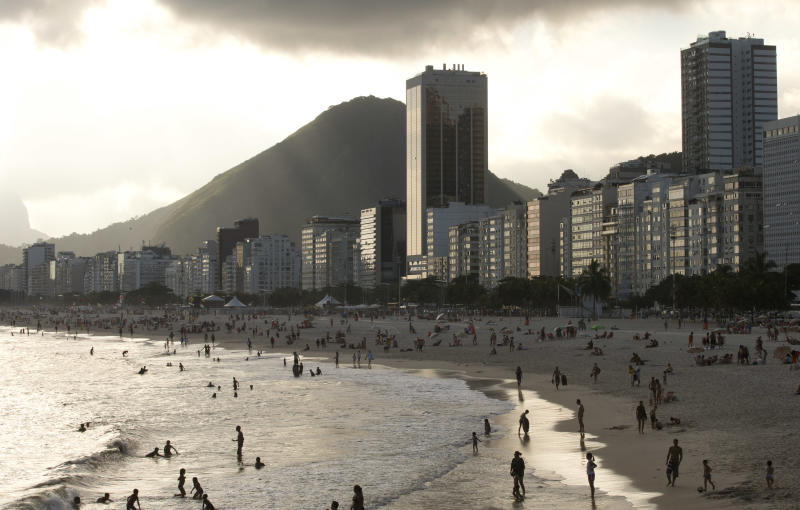 Hotels and apartment buildings line the Copacabana beach shore in Rio de Janeiro, Brazil, Thursday, Dec. 26, 2013. Sports fans on a budget may want to bypass the World Cup and wait until the 2016 Olympics before making a trip to Brazil, especially considering estimated hotel rates in Rio de Janeiro during both events. The rates are already about 100 percent more expensive, although such increases are considered normal in cities hosting big events. (AP Photo/Silvia Izquierdo)