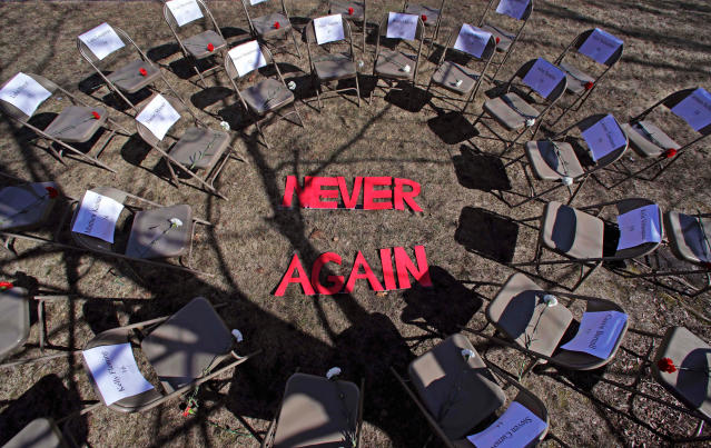 "<p>Two rings of chairs encircle the words ""NEVER AGAIN"" in a silent protest on the 19th anniversary of the Columbine High School shooting outside Trinity High School in Manchester, N.H., Friday, April 20, 2018. The inner ring chairs have names of the Columbine victims, the outer ring chairs have names of the Parkland High School shooting victims. (Photo: Charles Krupa/AP) </p>"