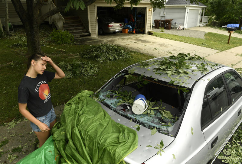 Sara Pilot, left, looks at the hail damage to her father's car outside of her home in Louisville, Colorado, on June 19. (Helen H. Richardson via Getty Images)