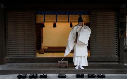 <span>A Shinto priest prepares to attend a ritual to mark the end of the year and prepare for the new one at Meiji Shrine in Tokyo</span> <span>Credit: Rex </span>