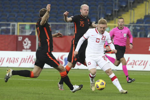 Poland's Kamil Jozwiak scores his side's first goal passing Netherlands' Daley Blind, left, and Netherlands' Davy Klaassen, rear, during the Nations League soccer match between Poland and The Netherlands at Silesian Stadium in Chorzow, Poland, Wednesday, Nov. 18, 2020. (AP Photo/Czarek Sokolowski)