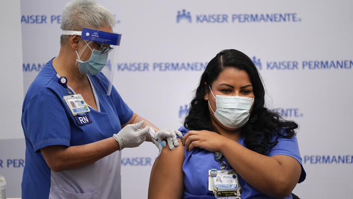 Nurse Helen Cordova wears a face mask and holds her rolled-up sleeve while she receives the Pfizer-BioNTech COVID-19 vaccine injection into her right arm