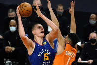 Denver Nuggets center Nikola Jokic shoots over Phoenix Suns guard Devin Booker (1) during the first half of an NBA basketball game Friday, Jan. 22, 2021, in Phoenix. (AP Photo/Rick Scuteri)