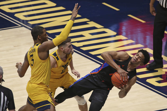 Florida guard Noah Locke (10) passes while defended by West Virginia forward Gabe Osabuohien (3) and guard Jordan McCabe (5) during the first half of an NCAA college basketball game Saturday, Jan. 30, 2021, in Morgantown, W.Va. (AP Photo/Kathleen Batten)