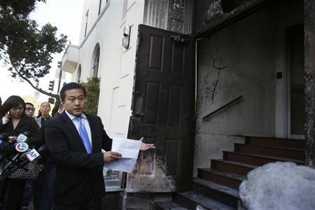 Wang Chuan, a spokesman for the Chinese consulate in San Francisco, points to a damaged door during a news conference after an unidentified person set fire in San Francisco, California January 2, 2014. REUTERS/Stephen Lam