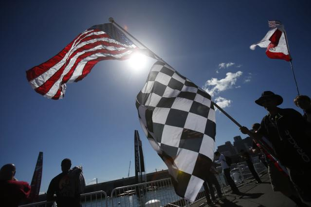 A sailing fan carries an American flag before Race 19 of the 34th America's Cup yacht sailing race between Oracle Team USA and Emirates Team New Zealand in San Francisco, California September 25, 2013. REUTERS/Stephen Lam (UNITED STATES - Tags: SPORT YACHTING)