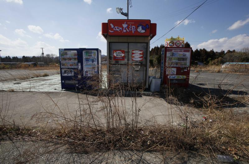 In this Tuesday, March 5, 2013 photo, weeds grow near drinks and rice vending machines in the abandoned town of Naraha, which was once inside the nuclear exclusion zone surrounding the crippled Fukushima Dai-ichi nuclear plant, in Japan. The town is now open to residents for short visits but they are unable to return to live. Workers have begun attempts to clean up the town, which was contaminated with radiation when the nuclear plant was crippled by a tsunami two years ago.  (AP Photo/Greg Baker)