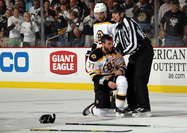 PITTSBURGH, PA - JUNE 01: Patrice Bergeron #37 of the Boston Bruins is helped up by linesman Pierre Racicot #65 following a fight with Evgeni Malkin #71 of the Pittsburgh Penguins (not pictured) during Game One of the Eastern Conference Final of the 2013 NHL Stanley Cup Playoffs at the Consol Energy Center on June 1, 2013 in Pittsburgh, Pennsylvania. (Photo by Bruce Bennett/Getty Images)
