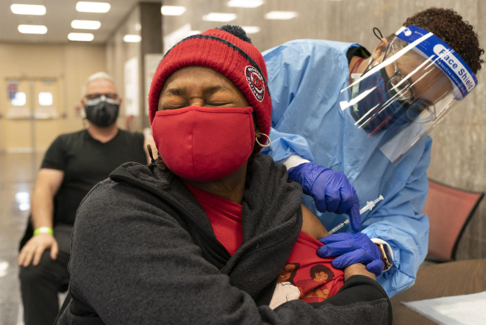 """In this Thursday, Feb. 11, 2021, photo Jorie Winbish, 56, of Washington, reacts as she receives her second dose of the COVID-19 vaccine at a clinic at Howard University, in Washington. """"I feel so lucky to have number two in my arm,"""" says Winbish. (AP Photo/Jacquelyn Martin)"""