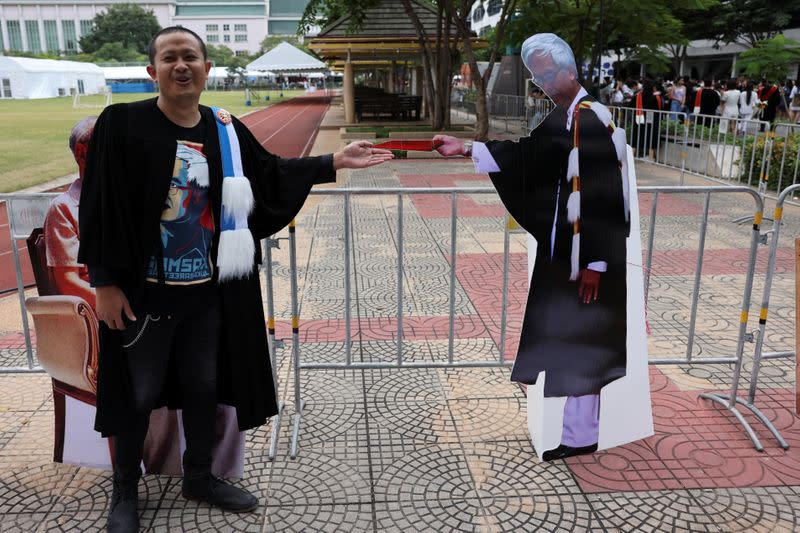 A student stands next to a cardboard figure of Somsak Jeamteerasakul, a Thai academic exiled, before his graduation ceremony, as some students have boycotted the ceremony because it is led by King Maha Vajiralongkorn, at Thammasat University in Bangkok