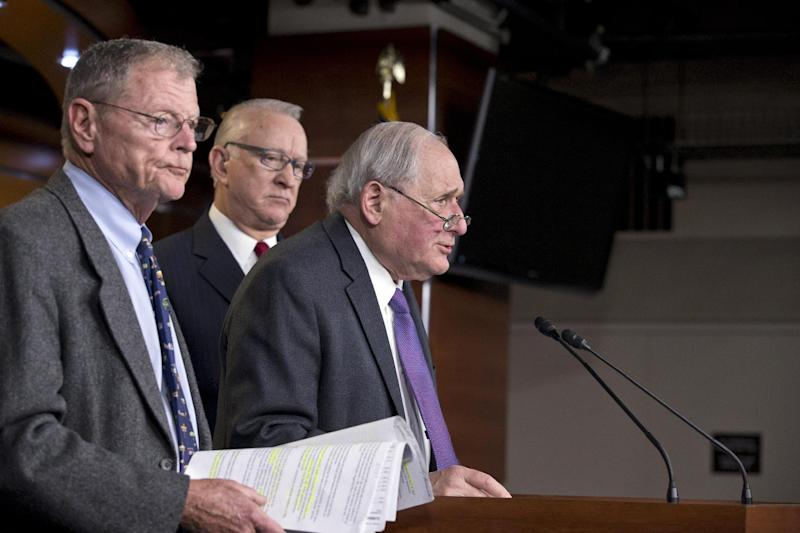 """From left, Sen. James Inhofe, R-Okla., the ranking member of the Senate Armed Services Committee, House Armed Services Committee Chairman Howard P. """"Buck"""" McKeon, R-Calif., and Senate Armed Services Committee Chairman Carl Levin, D-Mich., tell reporters they have reached an agreement on defense authorization, at a news conference on the Defense Authorization Bill, at the Capitol in Washington, Monday, Dec. 9, 2013. (AP Photo/J. Scott Applewhite)"""