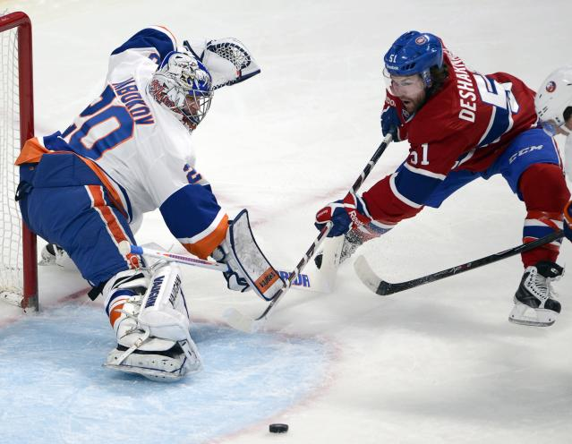 New York Islanders goalie Evgeni Nabokov (20) makes the save on Montreal Canadiens center David Desharnais (51) during the first period of an NHL hockey game Thursday, April 10, 2014, in Montreal. (AP Photo/The Canadian Press, Ryan Remiorz)
