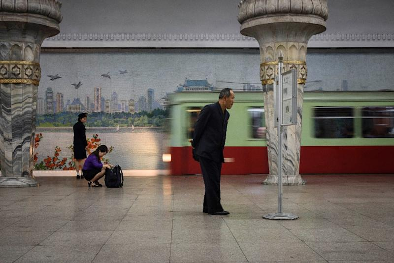 Commuters can read the newspaper at subway stations in Pyongyang (AFP Photo/Ed JONES)