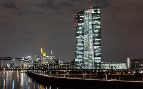 The European Central Bank (ECB) headquarters, right, are illuminated by light as the building stands on the skyline by the River Main in Frankfurt, Germany, on Friday, March 6, 2015. The final countdown is under way for the European Central Bank's program of government-bond purchases, which already fueled a debt-market rally that sent yields across the euro region to record lows. Photographer: Martin Leissl/Bloomberg Image title: GERMANY ECB BUILDING Credit: Martin Leissl Filename: TELEMMGLPICT000056783110.jpeg - Credit: Martin Leissl/Bloomberg