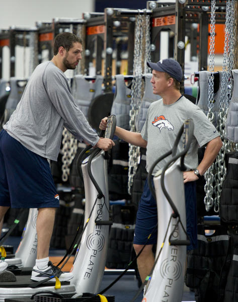 This photo provided the Denver Broncos shows Jacob Tamme, left, and quarterback Peyton Manning during workouts in the weight room at the NFL team's football headquarters in Englewood, Colo., on Monday, April 16, 2012. (AP Photo/Denver Broncos, Eric Bakke)