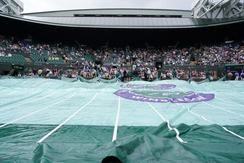 The rain covers are pulled over No. 1 Court during a rain delay on day two of the Wimbledon Tennis Championships in London, Tuesday June 29, 2021. (AP Photo/Alberto Pezzali)