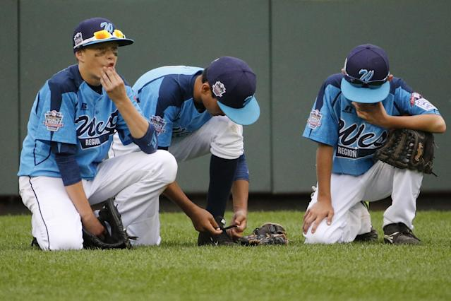 Las Vegas' Dallan Cave, left, Alex Barker, center, and Zach Hare kneel in the outfield during a play review in the fourth inning of the U.S. final against Chicago at the Little League World Series baseball tournament in South Williamsport, Pa., Saturday, Aug. 23, 2014. Chicago won 7-5. (AP Photo/Gene J. Puskar