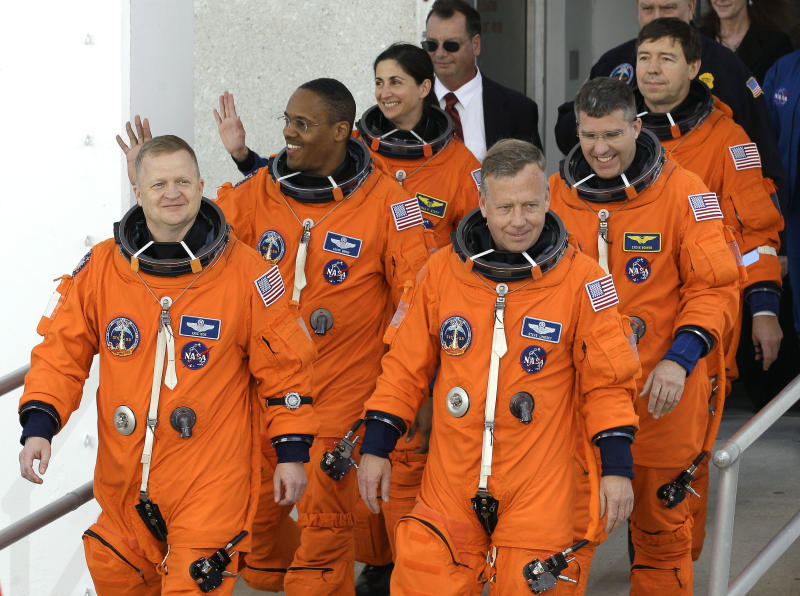 STS-133 crew members, front row from left, pilot Eric Boe, commander Steve Lindsey, second row, mission specialist Alvin Drew, Steve Bowen, third row from left, Nicole Stott, and Michael Barratt, leave the Operations and Checkout Building at the Kennedy Space Center in Cape Canaveral, Fla., for a trip to the launch pad Thursday, Feb. 24, 2011. The space shuttle Discovery is scheduled to lift off this afternoon on an 11-day mission to the international space station. (AP Photo/Chris O'Meara)