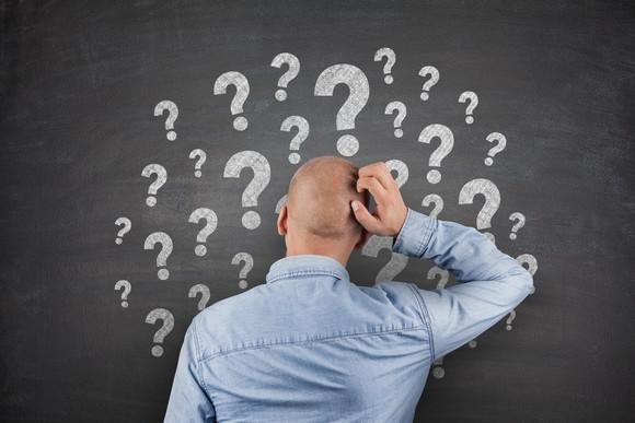 Man scratching head in front of chalkboard with many question marks drawn on it