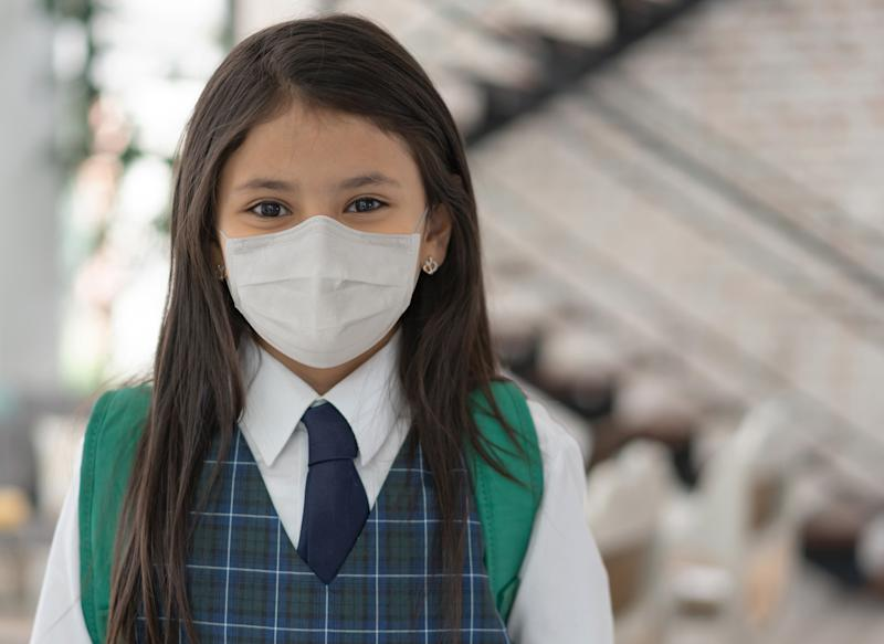 Portrait of a girl going to school wearing a facemask to avoid the spread of coronavirus - lifestyle during the COVID-19 pandemic concepts (Portrait of a girl going to school wearing a facemask to avoid the spread of coronavirus - lifestyle duri