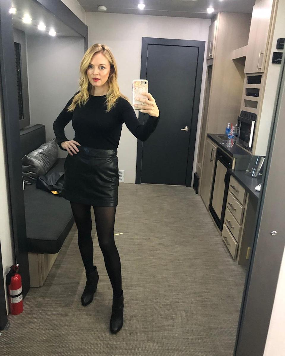 Heather Graham in a leather skirt and black top and black tights