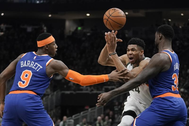 Milwaukee Bucks' Giannis Antetokounmpo is fouled driving between New York Knicks' Julius Randle and RJ Barrett during the second half of an NBA basketball game Tuesday, Jan. 14, 2020, in Milwaukee. (AP Photo/Morry Gash)