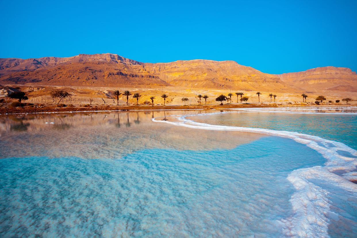 """The region surrounding this landlocked&nbsp;natural wonder is <a href=""""https://www.theguardian.com/environment/2017/mar/29/dead-sea-evidence-unprecedented-drought-future-warning-climate-change"""" rel=""""nofollow noopener"""" target=""""_blank"""" data-ylk=""""slk:facing its worst drought in centuries"""" class=""""link rapid-noclick-resp"""">facing its worst drought in centuries</a>, which is causing the <a href=""""http://www.bbc.com/news/world-middle-east-36477284"""" rel=""""nofollow noopener"""" target=""""_blank"""" data-ylk=""""slk:sea&rsquo;s surface level to drop"""" class=""""link rapid-noclick-resp"""">sea&rsquo;s surface level to drop</a>&nbsp;by a meter every year. Tourist resorts and landmarks that were on the shore in the 1980s are now <a href=""""http://www.bbc.com/news/world-middle-east-36477284"""" rel=""""nofollow noopener"""" target=""""_blank"""" data-ylk=""""slk:more than a mile&rsquo;s walk"""" class=""""link rapid-noclick-resp"""">more than a mile&rsquo;s walk</a>&nbsp;from the water, the BBC reports. <a href=""""http://www.cnn.com/2016/11/20/travel/cnnphotos-dead-sea-dying/"""" rel=""""nofollow noopener"""" target=""""_blank"""" data-ylk=""""slk:Humans have contributed to the shrinkage"""" class=""""link rapid-noclick-resp"""">Humans have contributed to the shrinkage</a>&nbsp;by diverting water sources and extracting minerals, while <a href=""""https://phys.org/news/2017-03-dead-sea-dire-drought.html"""" rel=""""nofollow noopener"""" target=""""_blank"""" data-ylk=""""slk:global warming"""" class=""""link rapid-noclick-resp"""">global warming</a>&nbsp;only <a href=""""http://www.earth.columbia.edu/articles/view/3352"""" rel=""""nofollow noopener"""" target=""""_blank"""" data-ylk=""""slk:makes the region ever drier"""" class=""""link rapid-noclick-resp"""">makes the region ever drier</a>."""
