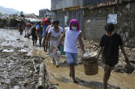 Residents retrieve belongings from their homes at the typhoon-damaged Kasiglahan village in Rodriguez, Rizal province, Philippines, Friday, Nov. 13, 2020. Thick mud and debris coated many villages around the Philippine capital Friday after Typhoon Vamco caused extensive flooding that sent residents fleeing to their roofs and killing dozens of people. (AP Photo/Aaron Favila)