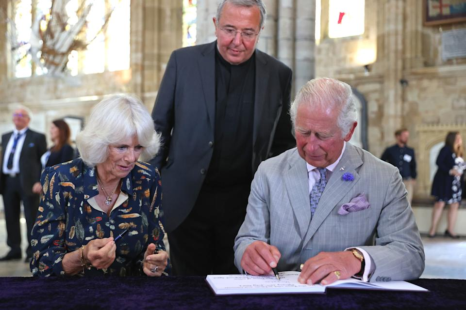 EXETER, UNITED KINGDOM - JULY 19: Camilla, Duchess of Cornwall  and Prince Charles, Prince of Wales sign the visitors book during a visit to Exeter Cathedral on July 19, 2021 in Exeter, United Kingdom. Founded in 1050, The Cathedral continues to offer daily Christian worship and choral music, alongside its roles as a community hub, heritage destination and venue for concerts and events. It is home to an extensive library and archive, housing important treasures such as the Exeter Book – thought to be the world's oldest surviving book of English literature. The visit celebrates the city's designation as a UNESCO City of Literature and launch of The Royal College of Nursing's Prince of Wales Nursing Cadet Scheme in England.  (Photo by Chris Jackson - WPA Pool/Getty Images)