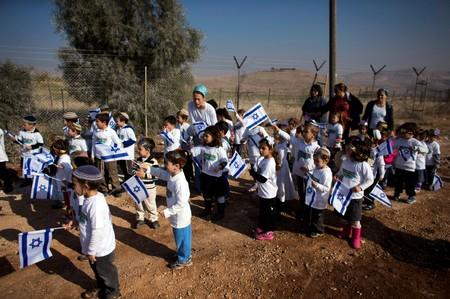 FILE PHOTO: Israeli children hold Israeli national flags as they wait ahead of a dedication ceremony of a new neighbourhood in a Jewish settlement in the Jordan Valley