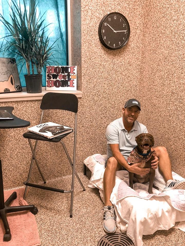 Scott Poore poses with Queen, a 3-year-old terrier mix, in their room at the Great Plains SPCA in Kansas City. (Credit: Scott Poore)