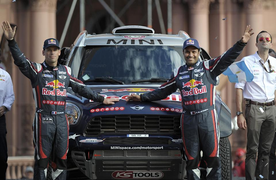 Qatar's driver Nasser Al-Attiyah (R) and co-driver Matthieu Baumel wave from their Mini during the symbolic start of the 2015 Dakar Rally in downtown Buenos Aires, on January 3, 2015 (AFP Photo/Alejandro Pagni)