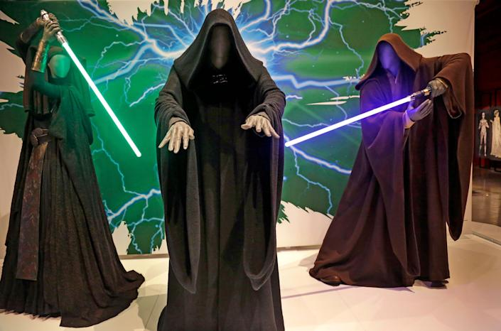 In this photo taken Thursday, Jan. 29, 2015, Sith robes and lightsabers are displayed as part of an exhibit on the costumes of Star Wars at Seattle'€™s EMP Museum. The creators of the new exhibit, with 60 original costumes from the six Star Wars movies, are hoping to gather geeks, fashionistas and movie fans together to discuss how clothing helps set the scene. The exhibit, Rebel, Jedi, Princess, Queen: Star Wars and the Power of Costume,€ will be in Seattle through early October and then travel across the United States through 2020. (AP Photo/Elaine Thompson)