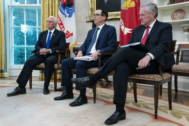 Vice President Mike Pence, left, Treasury Secretary Steven Mnuchin, centre, and White House chief of staff Mark Meadows listen as President Trump speaks at the start of the meeting (Evan Vucci/AP)