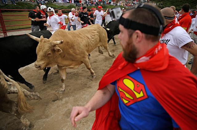 Participants run alongside charging bulls during the Great Bull Run at the Georgia International Horse Park, Saturday, Oct. 19, 2013, in Conyers, Ga. The event, expected to attract 3,000 runners Saturday, is inspired by the annual running of the bulls in Pamplona, Spain and has future stops planned in Texas, Florida, California, Illinois and Pennsylvania. (AP Photo/David Goldman)