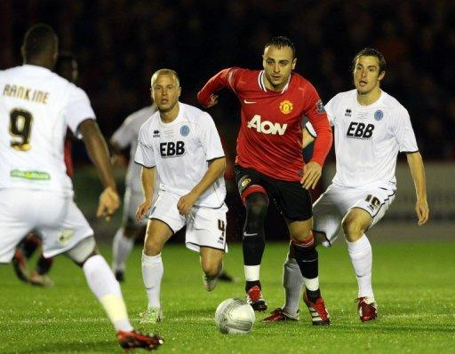 Manchester United's Dimitar Berbatov takes on Aldershot Town's Luke Guttridge (2nd L) and Danny Hylton (R) during their Carling Cup fourth round match. United won 3-0