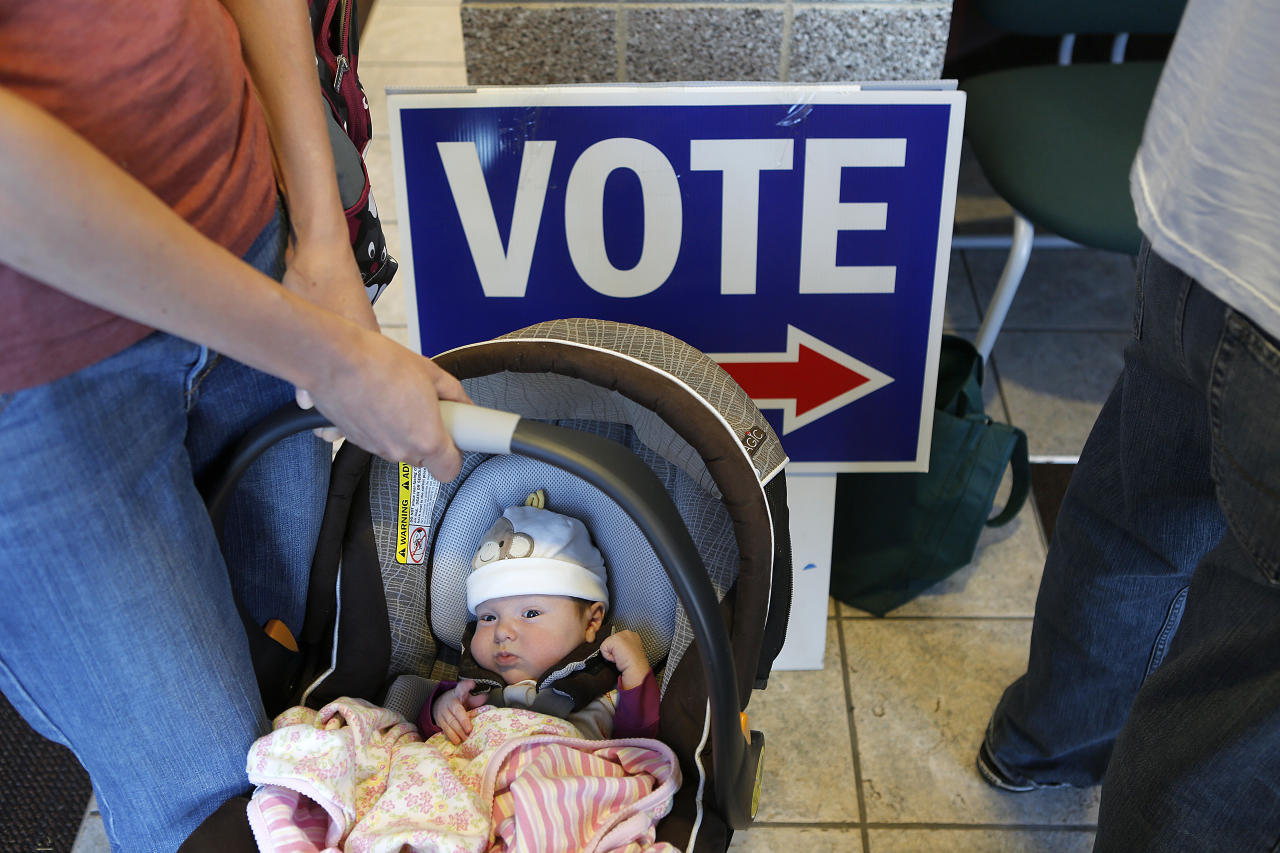 Lucille Sylvester of Boulder, Colorado holds her six-week-old daughter Cora Brehler as they wait in line to vote at the Boulder County Clerk and Recorder's Office on November 6, 2012 in Boulder, Colorado. Colorado is considered by most experts to be a key battleground state in this year's election. (Photo by Marc Piscotty/Getty Images)
