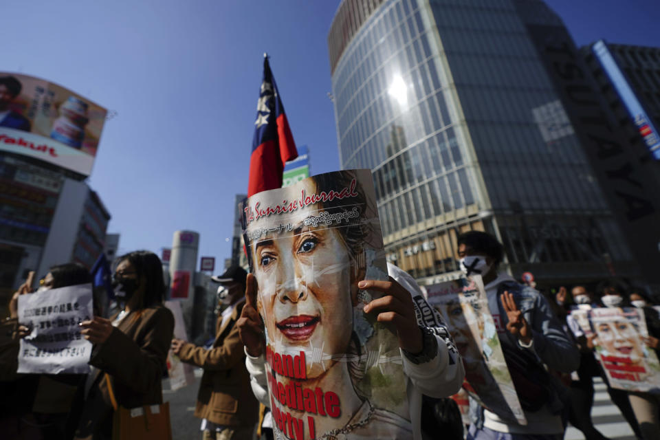 Myanmar people living in Japan and supporters march with portraits of Myanmar's ousted leader Aung San Suu Kyi through Shibuya pedestrian crossings during a protest in Sunday, Feb. 14, 2021, in Tokyo. Thousands of people from Myanmar living in Japan have marched in downtown Tokyo to protest the military coup back home. (AP Photo/Eugene Hoshiko)