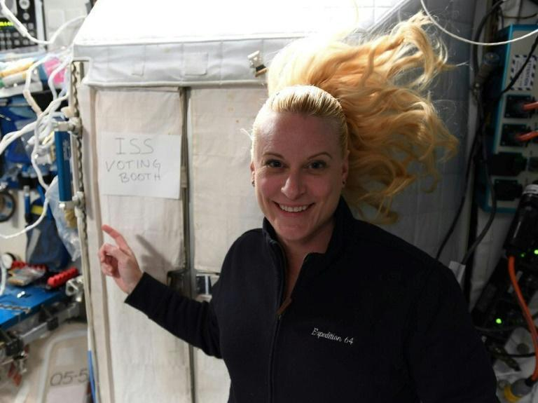 "This handout photo released on October 22, 2020 by NASA shows International Space Station crew member Kate Rubins pointing to a sign reading ""ISS voting booth"""