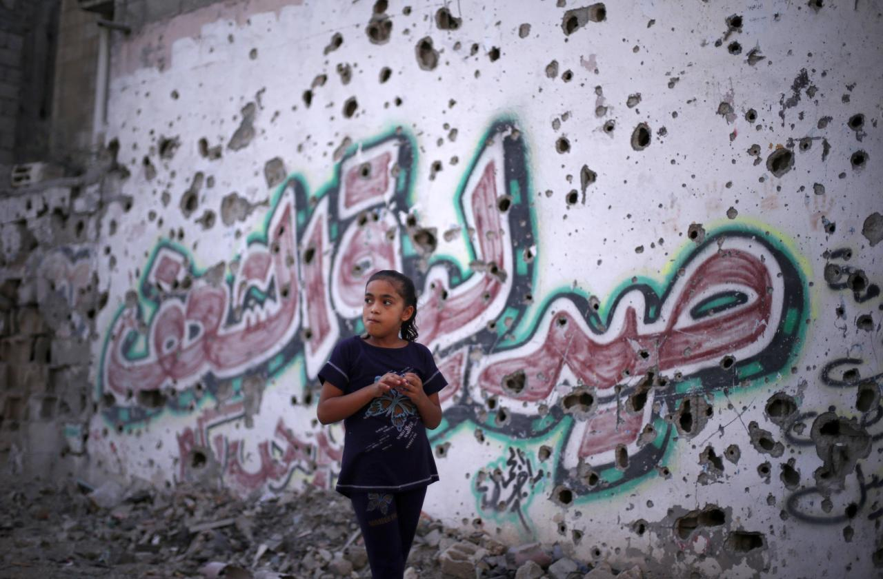 """A Palestinian girl walks past a pharmacy's wall, which witnesses said was damaged during the Israeli offensive, in the east of Gaza City September 10, 2014. An open-ended ceasefire between Israel and Hamas-led Gaza militants, mediated by Egypt, took effect on August 26 after a seven-week conflict. It called for an indefinite halt to hostilities, the immediate opening of Gaza's blockaded crossings with Israel and Egypt, and a widening of the territory's fishing zone in the Mediterranean. The writing on the wall reads """"Al-Sha'af Pharmacy"""". REUTERS/Suhaib Salem (GAZA - Tags: POLITICS CIVIL UNREST SOCIETY TPX IMAGES OF THE DAY)"""