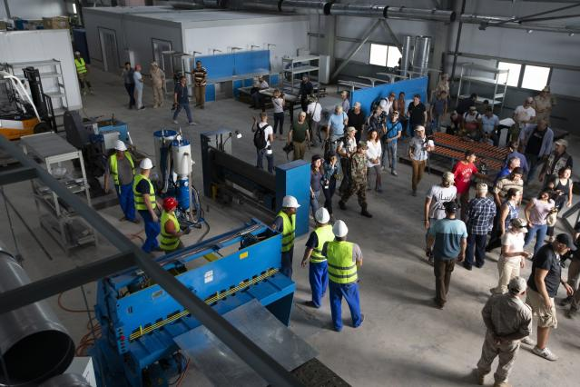 Foreign journalists walk through the shipyard at the Russian naval facility speaks to foreign journalists in Tartus, Syria, Thursday, Sept. 26, 2019. Russia has a naval base in Tartus, the only such facility it has outside the former Soviet Union. (AP Photo/Alexander Zemlianichenko)