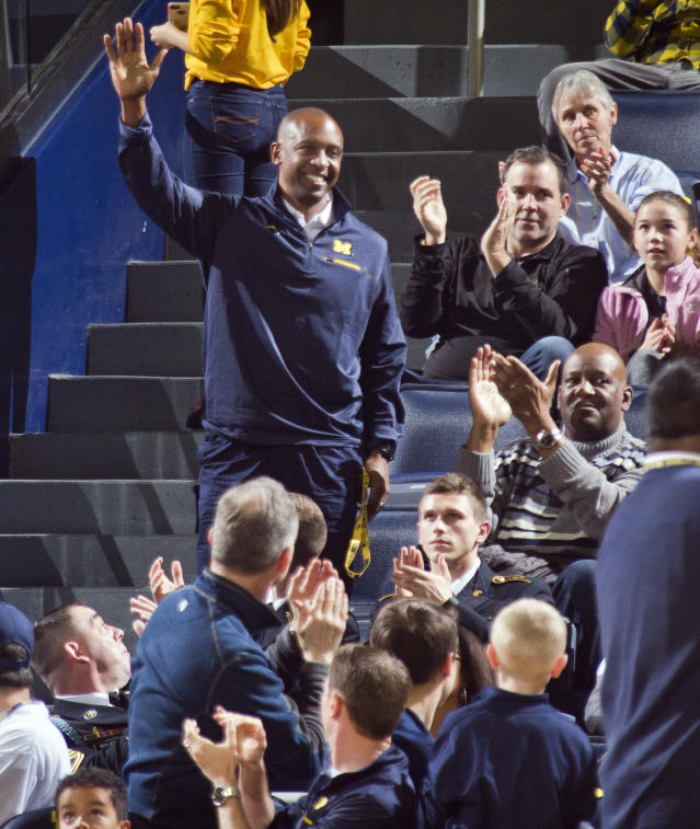 FILE - In this Jan. 21, 2017, file photo, newly hired Michigan football assistant head coach Pep Hamilton acknowledges the crowd as he is being introduced during the first half of an NCAA college basketball game between Michigan and Illinois, at Crisler Center in Ann Arbor, Mich. Minorities make up only 19 percent of Division I head football coaches and less across the Power Five conferences: the ACC, SEC, Big Ten, Big 12 and Pac 12. (AP Photo/Tony Ding, File)
