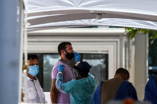 """A medical personnel member takes samples on a man at a """"walk-in"""" and """"drive-through"""" coronavirus testing site in Miami Beach, Florida on June 24, 2020"""