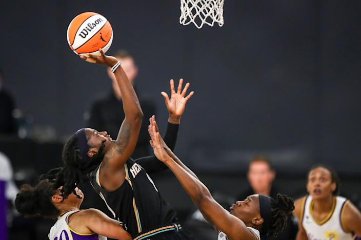 A basketball player shoots as she leaps above multiple hands trying to block her.