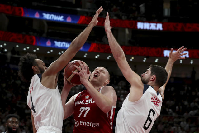 Poland's Damian Kulig is blocked by United States' Derrick White at left and United States' Joe Harris at right during a consolation playoff game for the FIBA Basketball World Cup at the Cadillac Arena in Beijing on Saturday, Sept. 14, 2019. U.S. defeated Poland 87-74 (AP Photo/Ng Han Guan)