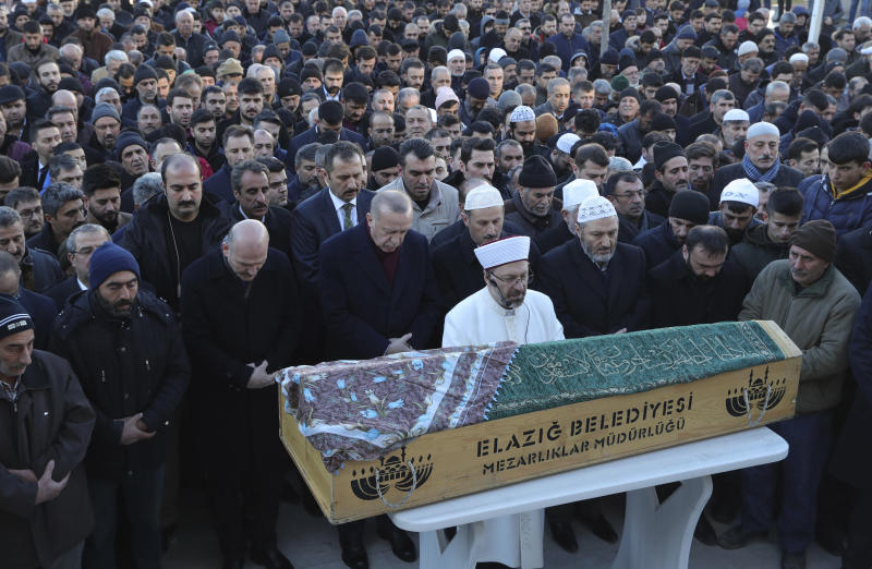 Turkey's President Recep Tayyip Erdogan, centre, attends q funeral procession for Salih Civelek and Aysegul Civelek, victims of Friday's earthquake in Elazig, eastern Turkey, Friday, during the Saturday, Jan. 25, 2020. Rescue workers were continuing to search for people buried under the rubble of apartment blocks in Elazig and neighbouring Malatya. Mosques, schools, sports halls and student dormitories were opened for hundreds who left their homes after the quake (Presidential Press Service via AP, Pool)