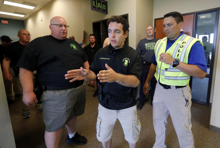 In this July 21, 2019 photo, Brian Ovens, left, looks on as Bryan Hetherington, center, ask a question of police officer and instructor Nick Guadarrama, right, during a security training session at Fellowship of the Parks campus in Haslet, Texas. While recent mass shootings occurred at a retail store in El Paso, Texas, and a downtown entertainment district in Dayton, Ohio, they were still felt in houses of worship, which haven't been immune to such attacks. And some churches have started protecting themselves with guns. (AP Photo/Tony Gutierrez)